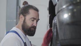 Mecânico farpado considerável do retrato que inspeciona a suspensão ou os freios na roda de carro do automóvel levantado no servi filme