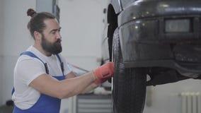 Mecânico farpado considerável que inspeciona a suspensão ou os freios na roda de carro do automóvel levantado na estação do servi vídeos de arquivo