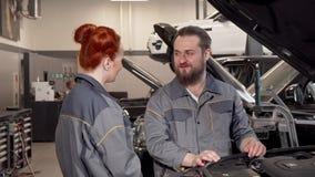 Mecânico farpado que fala a seu coleague fêmea na oficina do automóvel filme