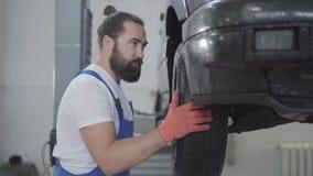 Mecânico farpado que inspeciona a suspensão ou os freios na roda de carro do automóvel levantado na estação do serviço de reparaç video estoque