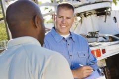 Mecânico Looking At Client ao escrever na prancheta Foto de Stock Royalty Free