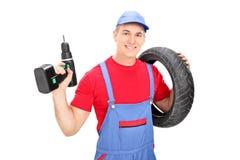 Mecânico masculino que guarda um pneu e uma broca Fotos de Stock
