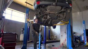 Mecânico masculino que usa o elevador hidráulico para levantar a peça do carro video estoque