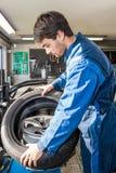 Mecânico Mounting Car Tire na liga Rim In Garage fotografia de stock royalty free