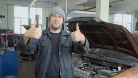 Mecânico na oficina de reparações do carro que mostra os polegares dobro acima vídeos de arquivo