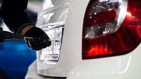 Mecânico no serviço do automóvel que faz operações manuais com o número de matrícula do carro Foto de Stock