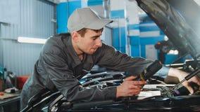 Mecânico nos macacões que olham à capa da reparação automobilístico do serviço do automóvel Fotos de Stock