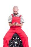 Mecânico novo que texting e que conversa no smartphone imagem de stock