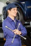 Mecânico pensativo Holding Rim Wrench At Garage fotos de stock