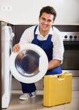 Mecânico profissional que repara a máquina de lavar Fotografia de Stock Royalty Free