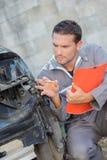 Mecânico que faz o carro danificado avaliação imagem de stock