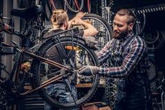 Mecânico que faz o manual do serviço da roda de bicicleta em uma oficina imagens de stock
