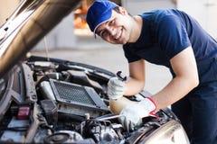 Mecânico que fixa um motor de automóveis Imagens de Stock