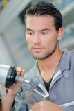 Mecânico que guarda a arma de pulverizador dos componentes imagem de stock