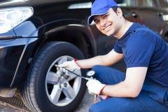 Mecânico que infla um pneu foto de stock