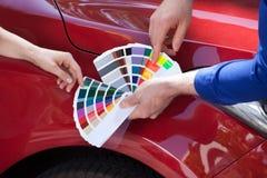 Mecânico que mostra amostras da cor ao cliente contra o carro Fotografia de Stock Royalty Free