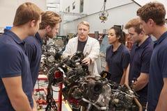 Mecânico que mostra as peças de um motor aos aprendizes, fim acima imagem de stock