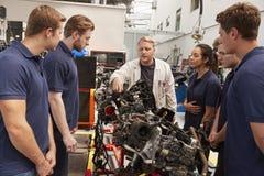 Mecânico que mostra as peças de um motor aos aprendizes, fim acima foto de stock