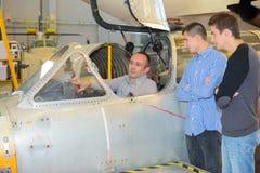 Mecânico que mostra homens novos dentro da cabina do piloto Imagem de Stock Royalty Free
