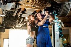 Mecânico que repara o carro no elevador hidráulico, menina que está em seguida o imagem de stock
