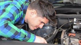 Mecânico que repara o motor Verificando a correia auxiliar vídeos de arquivo