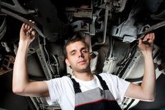 Mecânico que trabalha abaixo do carro no uniforme com chave Fotografia de Stock Royalty Free