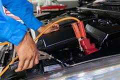 Mecânico que une cabos de ligação em ponte com o close up automobilístico da bateria Foto de Stock