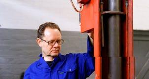 Mecânico que usa o elevador hidráulico na garagem 4k video estoque
