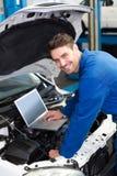 Mecânico que usa o portátil no carro Fotos de Stock Royalty Free