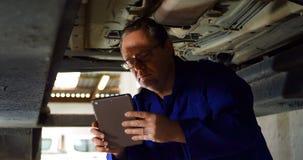 Mecânico que usa a tabuleta digital ao examinar um carro 4k filme