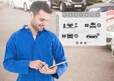 Mecânico que usa a tabuleta digital com relação do mecânico de carro no fundo Imagem de Stock