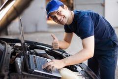 Mecânico que usa um laptop para verificar um motor de automóveis Fotografia de Stock Royalty Free