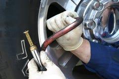 Mecânico que verific o preasure do pneu Fotografia de Stock