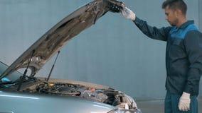 Mecânico que verifica o nível de óleo em uma oficina do carro Homem no motor do serviço do caminhão Imagens de Stock Royalty Free