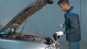 Mecânico que verifica o nível de óleo em uma oficina do carro Homem no motor do serviço do caminhão Fotos de Stock
