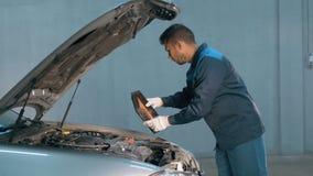 Mecânico que verifica o nível de óleo em uma oficina do carro Homem no motor do serviço do caminhão Fotografia de Stock