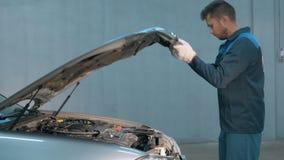 Mecânico que verifica o nível de óleo em uma oficina do carro Homem no motor do serviço do caminhão Imagem de Stock