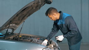 Mecânico que verifica o nível de óleo em uma oficina do carro Homem no motor do serviço do caminhão Imagem de Stock Royalty Free