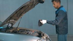 Mecânico que verifica o nível de óleo em uma oficina do carro Homem no motor do serviço do caminhão Fotos de Stock Royalty Free