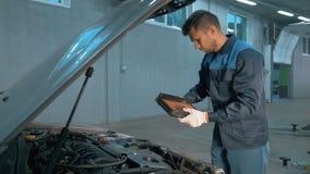 Mecânico que verifica o nível de óleo em uma oficina do carro Homem no motor do serviço do caminhão Fotografia de Stock Royalty Free