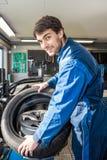 Mecânico seguro Mounting Car Tire em Rim In Garage foto de stock