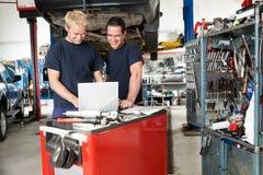 Mecânicos com o portátil na garagem Imagem de Stock Royalty Free