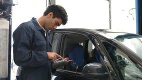 Mecânicos consideráveis que revisam um carro vídeos de arquivo