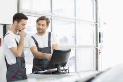 Mecânicos de automóvel masculinos que conversam na oficina de reparações Fotos de Stock