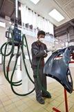 Mecânicos de carro profissionais que lustram o amortecedor do carro Fotografia de Stock