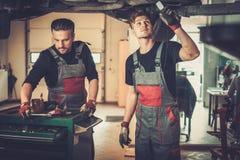 Mecânicos de carro profissionais que trabalham sob o carro levantado no serviço de reparação de automóveis fotos de stock