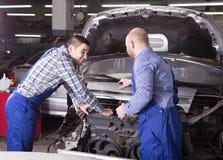 Mecânicos de carro que trabalham no carshop Fotografia de Stock Royalty Free