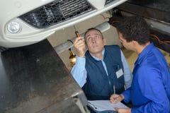 Mecânicos de sorriso especializados nas combinações que trabalham sob o carro Imagens de Stock