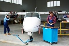 Mecânicos do aeroporto que fixam o plano Imagens de Stock