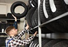 Mecânicos masculinos novos com pneus de carro Foto de Stock Royalty Free